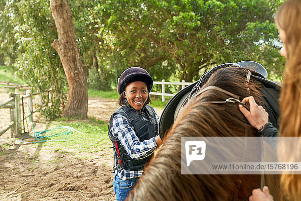 Portrait confident girl preparing saddle for horseback riding