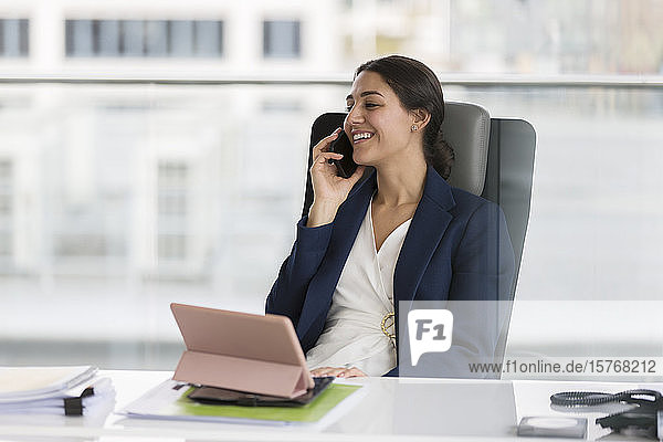 Lächelnde Geschäftsfrau  die im Büro mit einem Smartphone telefoniert