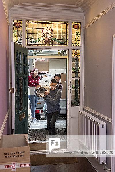 Freunde ziehen um und tragen einen Teppich durch die Haustür