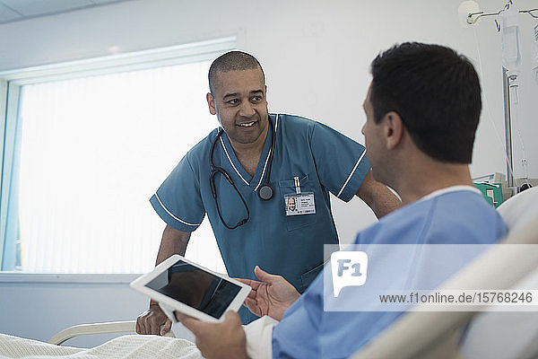Male nurse talking with patient using digital tablet in hospital bed