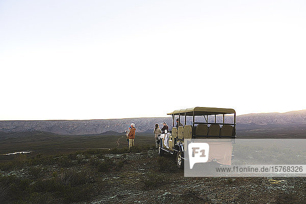 Safari tour group and off-road vehicle on remote hill at sunrise