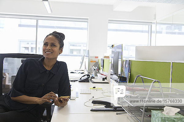 Smiling businesswoman using smart phone in open plan office