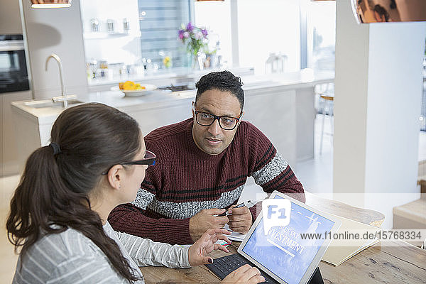 Couple financial planning at digital tablet in kitchen
