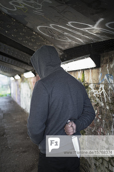 Dangerous young man holding knife weapon behind back in urban tunnel