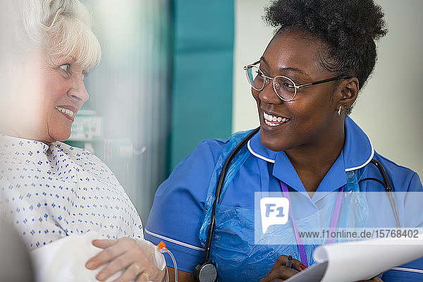 Friendly female nurse talking with senior patient in hospital