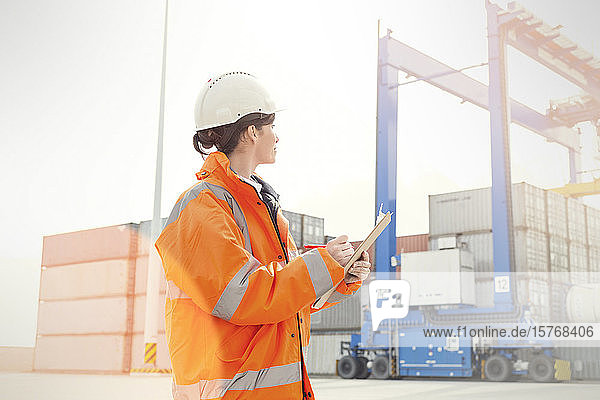 Female dock manager with clipboard watching cargo containers
