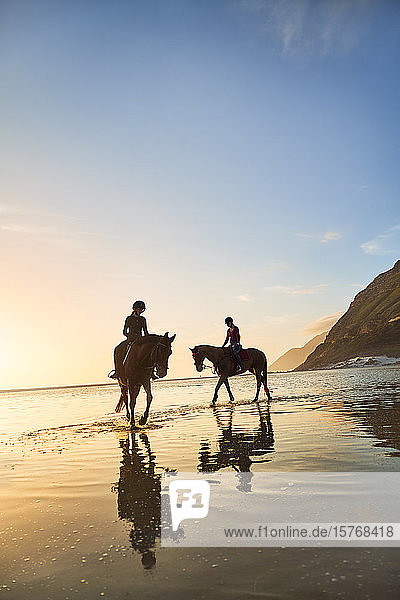 Young women horseback riding on tranquil sunset beach