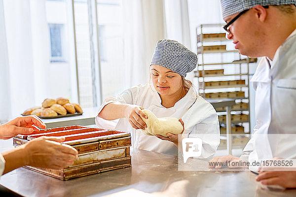 Junge Schüler mit Down-Syndrom backen Brot im Unterricht