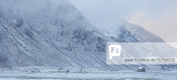 Snow covered mountain and remote cabin Flakstad Lofoten Norway