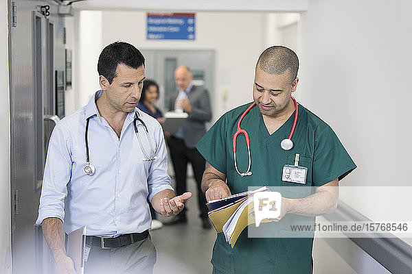 Male doctor and surgeon discussing medical chart  making rounds in hospital corridor