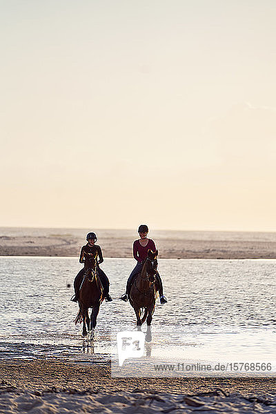 Young women horseback riding in ocean surf