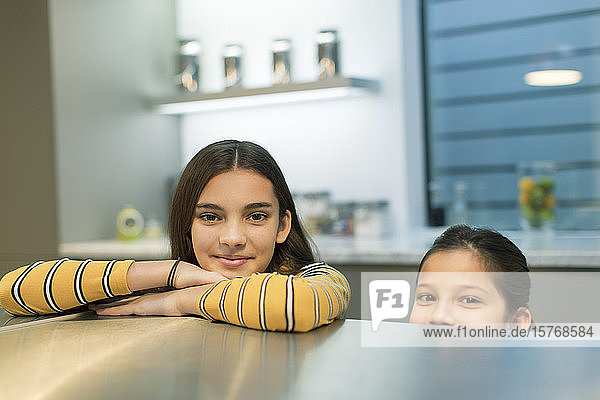 Portrait smiling sisters in kitchen