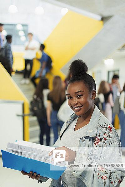 Portrait confident junior high girl student studying in corridor