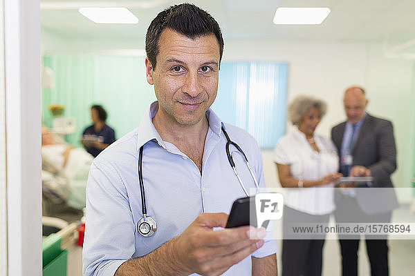 Portrait confident male doctor using smart phone in hospital ward