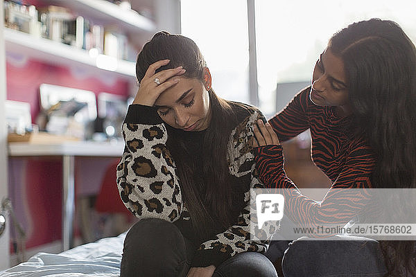 Teenager-Mädchen tröstet verstörten Freund auf dem Bett