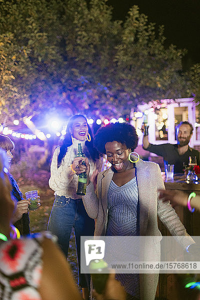 Happy friends dancing and drinking at garden party
