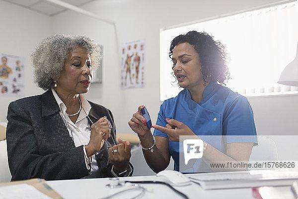 Ärztin unterrichtet Diabetes-Patienten im Umgang mit dem Blutzuckermessgerät in einer Arztpraxis
