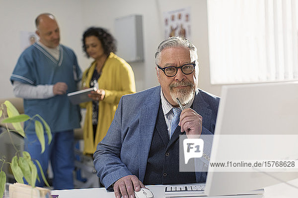 Portrait confident male doctor working at computer in doctors office