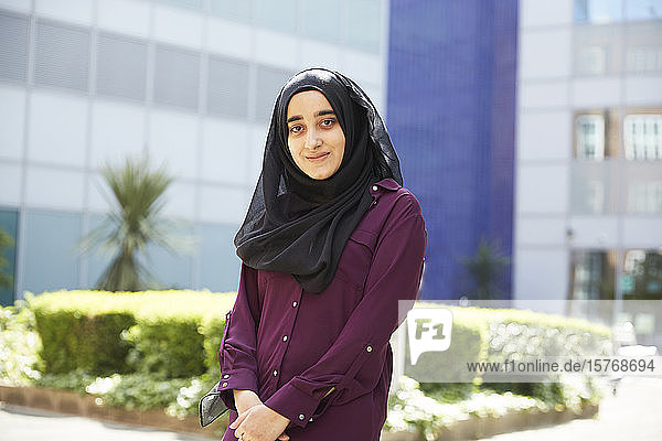Portrait confident young woman in hijab outside sunny building