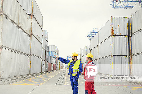 Dock workers talking among cargo containers at shipyard