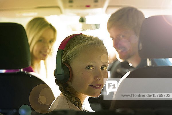 Portrait smiling girl with headphones riding in back seat of car