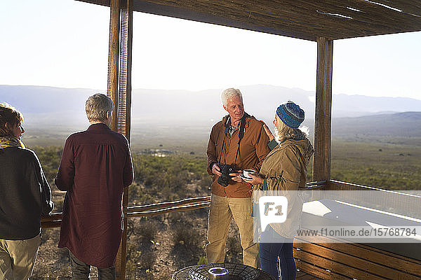 Senior couple with camera and tea on sunny safari lodge balcony