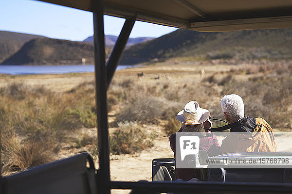 Senior couple on safari looking at view outside off-road vehicle