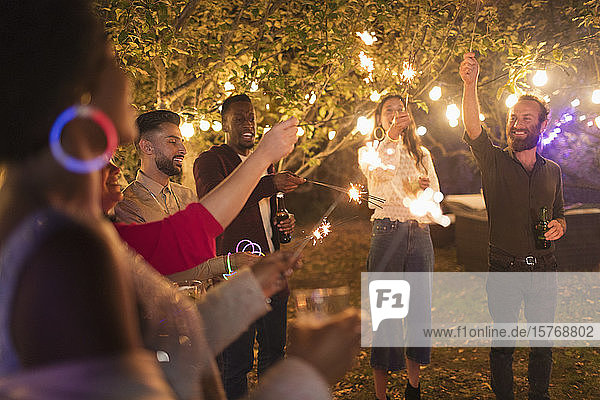 Playful friends with sparklers enjoying garden party Playful friends with sparklers enjoying garden party