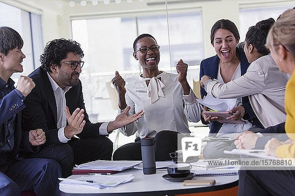 Aufgeregte Geschäftsleute jubeln in der Sitzung