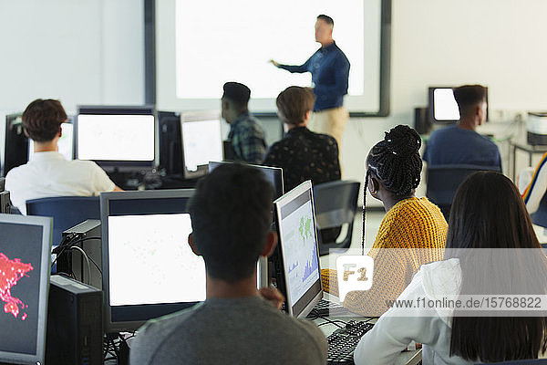 Junior high students at computers watching teacher at projection screen in classroom