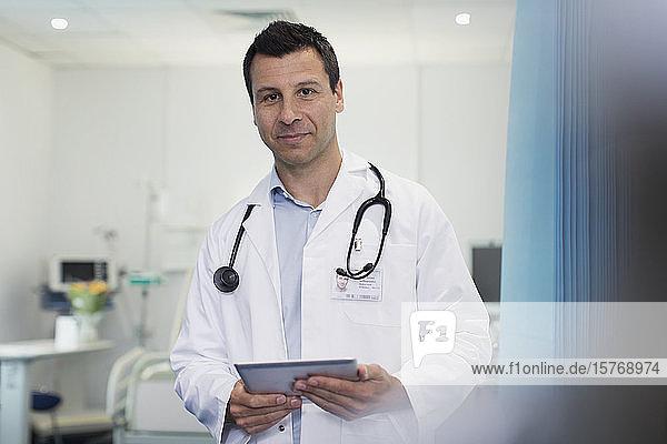 Portrait confident male doctor using digital tablet in hospital room