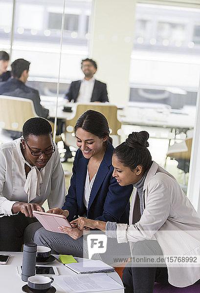Smiling businesswomen using digital tablet in meeting
