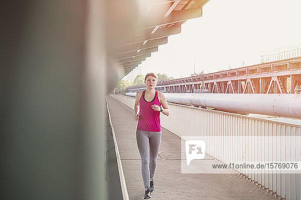 Young woman running on urban train station platform