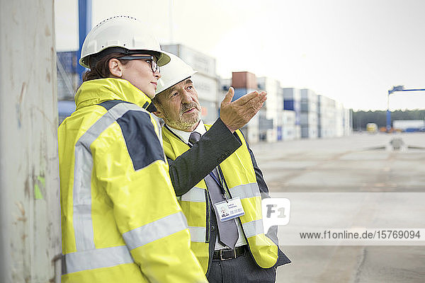 Dock manager and worker talking at shipyard