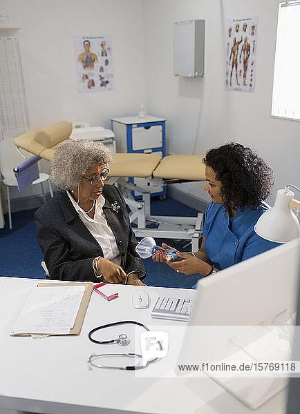 Eine Ärztin unterrichtet einen älteren Patienten in der Verwendung eines Inhalators in einer Arztpraxis