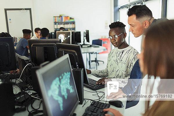 Male junior high teacher helping boy student using computer in computer lab