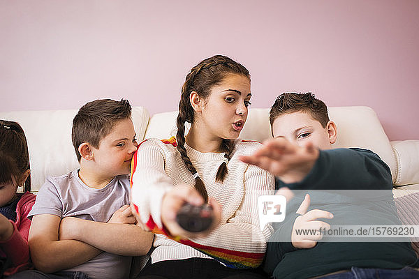 Siblings with remote control watching TV on sofa