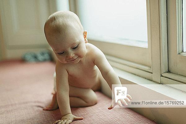 Cute baby girl on window seat