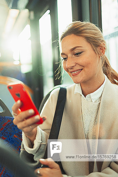Young woman using smart phone on bus