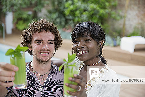 Portrait happy multiethnic young couple drinking cocktails poolside