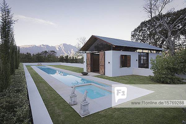 Idyllic  luxury lap pool and pool house with mountains in the background