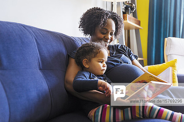 Pregnant mother and daughter reading book on sofa
