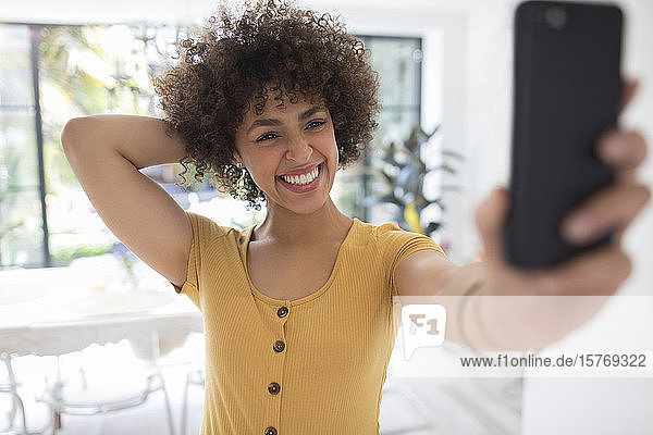Happy confident young woman taking selfie with smart phone
