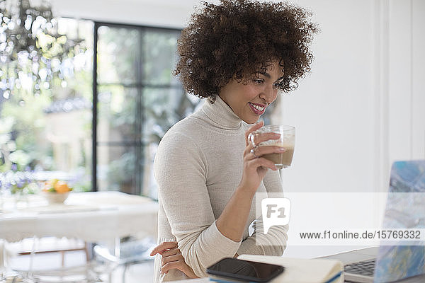 Young female freelancer drinking coffee at laptop