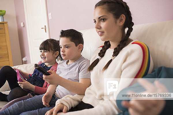 Boy with Down Syndrome watching TV with siblings on sofa