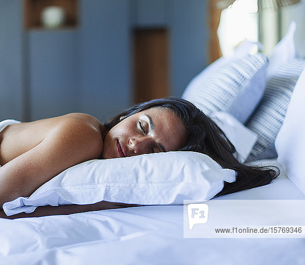 Serene young woman sleeping on pillow in bed