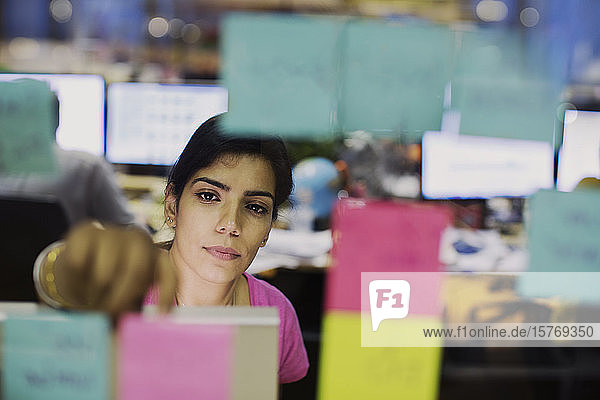 Dedicated businesswoman with adhesive notes planning in office