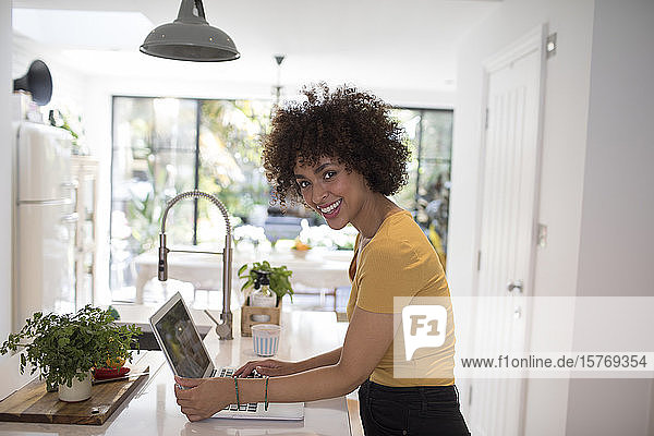 Portrait happy young female freelancer working at laptop in kitchen