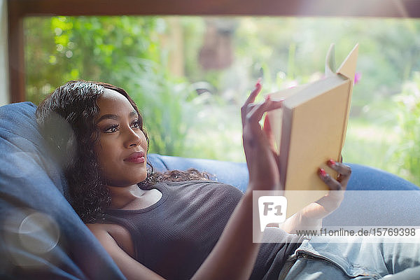 Young woman relaxing reading book in beanbag chair