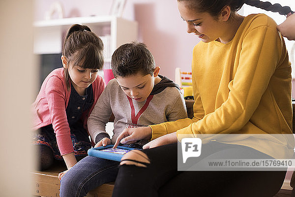 Brother and sisters using digital tablet